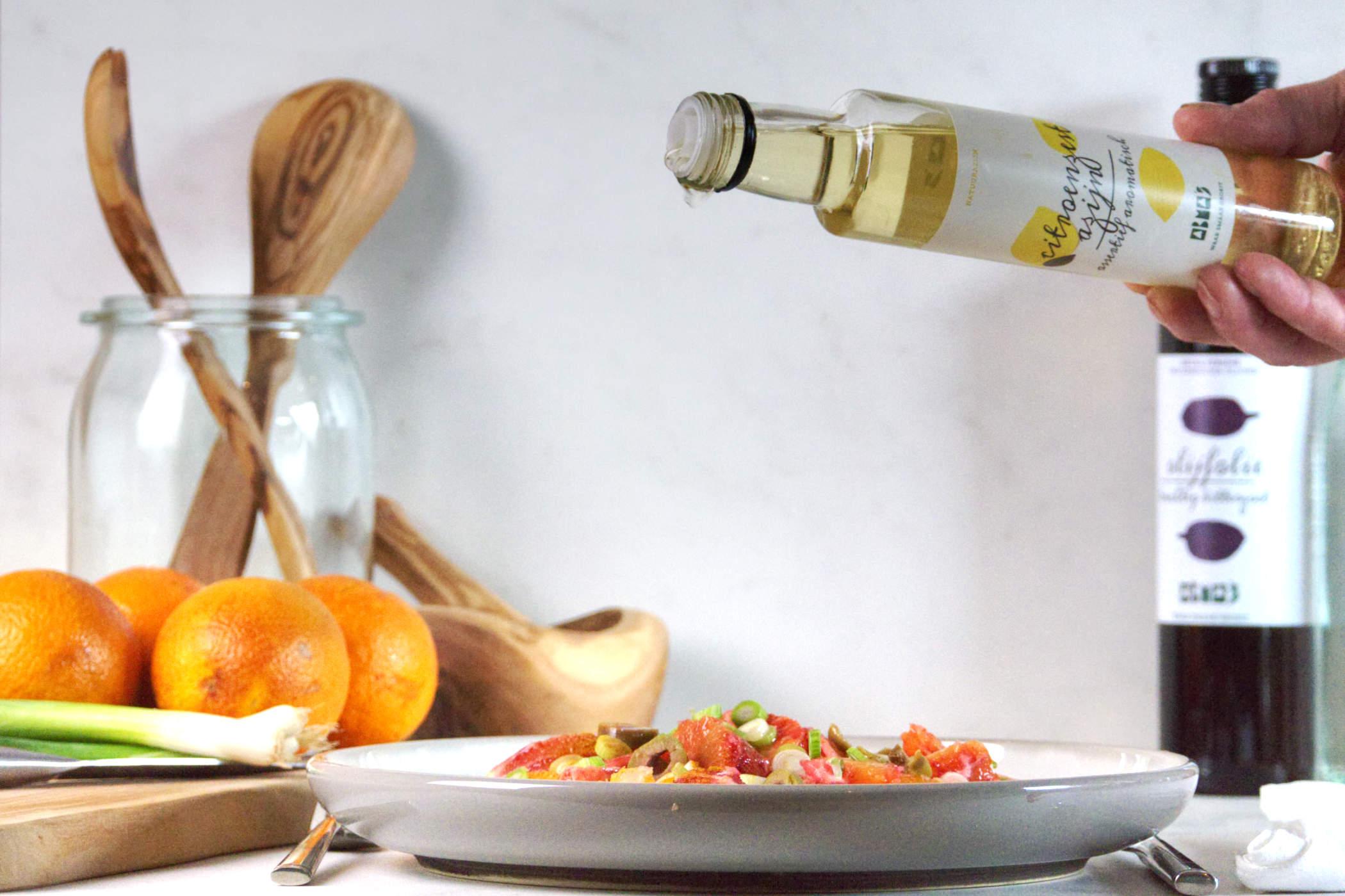 Abma's Citroenzest azijn wordt over een salade geschonken.